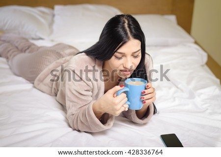 Sexy beautiful woman in bed drinking coffee tea with smartphone, portrait close up
