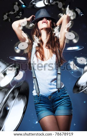sexy beautiful woman in hat and shorts with suspenders and vinyl racords - stock photo