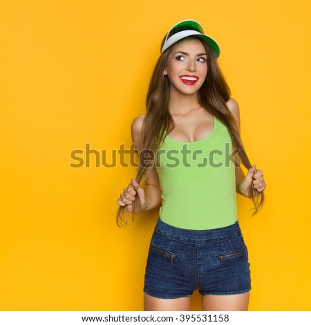 Sexy beautiful woman in jeans shorts and lime green shirt holding her long hair in hands, smiling and looking away. Three quarter length studio shot on yellow background. - stock photo