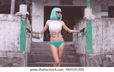 Sexy beautiful woman in modern futuristic style posing over abandoned building. Creative look of woman on the beach wearing bikini, black leather fingerless and blue wig