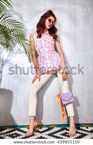 Sexy beautiful woman luxury chic fashion brand handbag trendy jewelry style for party date glamour pose summer palm clothes collection brunette hair accessory model wear cotton blouse trousers, hairdo - stock photo