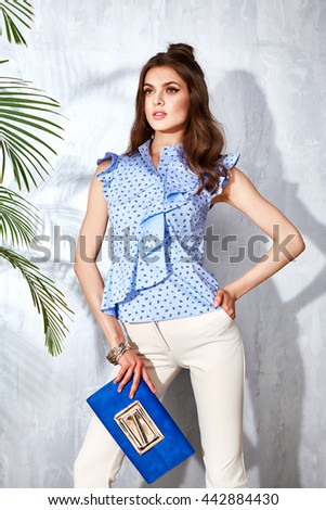 Sexy beautiful woman luxury chic fashion brand handbag trendy jewelry style for party date glamour pose summer palm clothes collection brunette hair accessory model wear blue cotton blouse trousers - stock photo