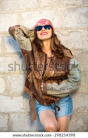 Sexy beautiful woman wearing leather coat, sexy shorts, sunglasses over grey grunge vintage wall