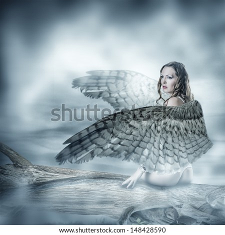 Sexy beautiful woman with birds wings with feathers sitting on a tree - stock photo
