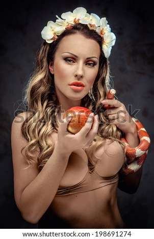 Sexy beautiful woman with red apple and snake, conceptual photo - stock photo