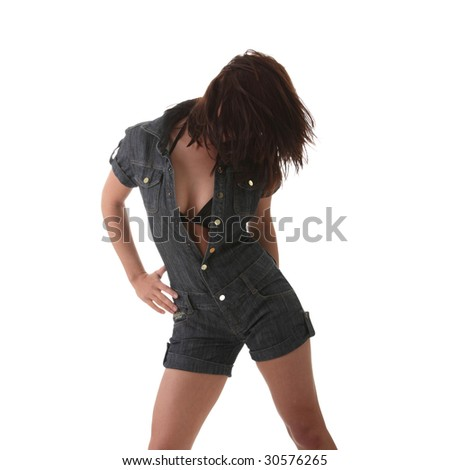 Sexy, beautiful, young woman dancing (hair flying) in jeans suit isolated on white background - stock photo