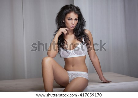 Sexy beautiful young woman posing in white lingerie. Girl with perfect body and long hair. Glamour makeup.  - stock photo