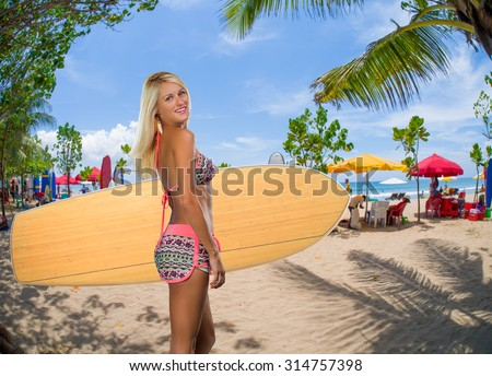 sexy beautiful young woman surfer girl in bikini with white surfboard at a beach in Bali indonesia - stock photo