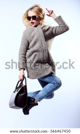 Sexy Beauty Girl. Fashion Blonde. Portrait of a girl dressed in grey coat, wearing a black bag, jump on a white studio background. - stock photo