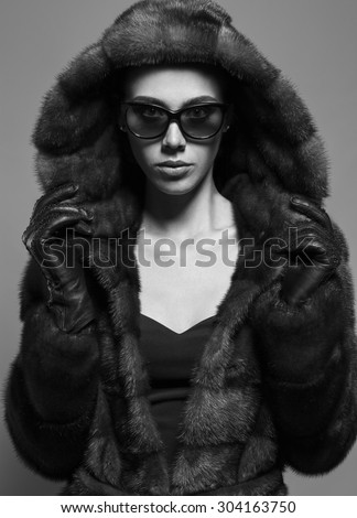 Sexy Beauty Girl with natural  Make up. Fashion Brunette  Portrait of a girl dressed in fur coat, black dress and sunglasses posing on grey background. Retro style. Monochrome (black and white) photo - stock photo