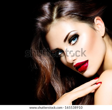 Sexy Beauty Girl with Red Lips and Nails. Provocative Make up. Luxury Woman with Blue Eyes. Fashion Brunette Portrait isolated on black background. Gorgeous Woman Face. Long Hair  - stock photo