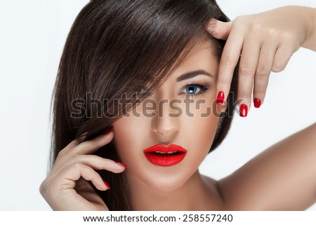Sexy Beauty Girl with Red Lips and Nails. Provocative Make up. Luxury Woman with Blue Eyes. Fashion Brunette Portrait isolated on a white background. Gorgeous Woman Face. Long Hair  - stock photo
