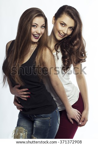 Sexy Beauty Girls (sisters, friends) with perfect make up, hairdo, wearing in casual clothes. Provocative Make up. Fashion  Portraits on white background. Gorgeous Woman Face. Long Hair. Isolated - stock photo