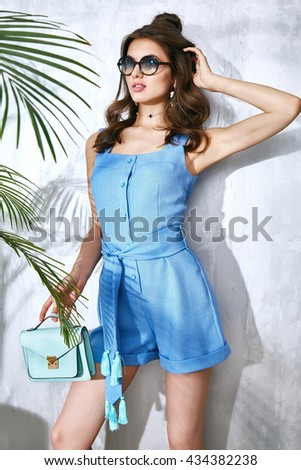 Sexy beauty woman in blue silk dress luxury chic fashion gold sunglasses brand hand bag trendy hat jewelry style for party date glamour pose summer palm clothes collection brunette hair - stock photo