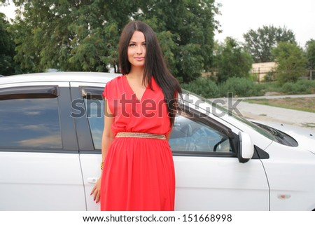 Sexy Beauty Woman In Fluttering Red Dress Standing near car - stock photo