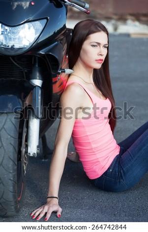 Sexy biker sitting next to sport bike - stock photo