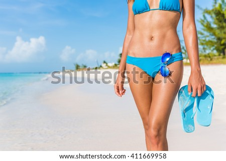 Sexy bikini body woman - abs, sunglasses, flip flops on beach vacation. Model showing slim abs and tanned skin on tropical caribbean travel destination vacation. Belly button stomach and thighs legs. - stock photo