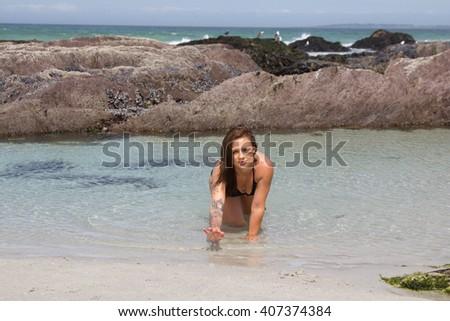 Sexy bikini model crawling out of the sea - stock photo