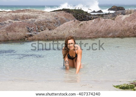 Sexy bikini model crawling out of the sea with copyspace - stock photo