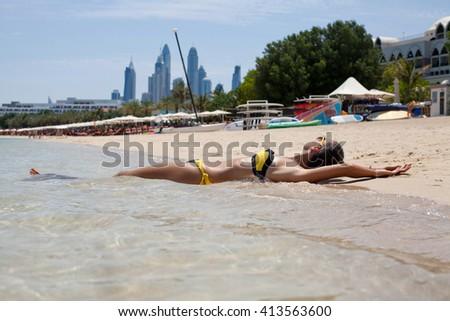 Sexy bikini woman relaxing with tanned slim body on beach vacation paradise getaway. Model lying down on sand beach sunbathing in UAE travel destination. - stock photo