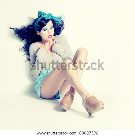 Sexy black haired pin up girl in blue shorts and wooden shoes; a lot of copyspace available; retro style image
