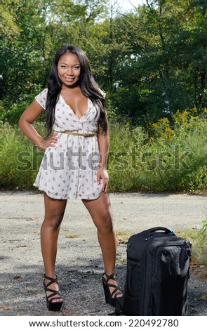 Sexy black woman staring along country road with bag waiting for ride - wearing short sundress