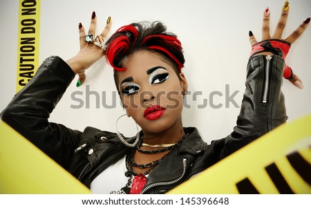 Sexy Black Woman Wrapped in Caution Tape leaning on wall. - stock photo
