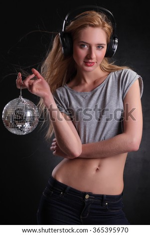 Sexy blond DJ is posing with sphere - stock photo