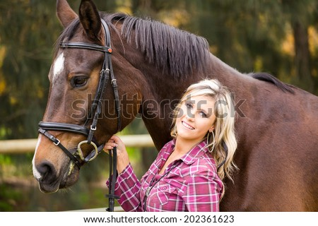 Sexy blond farm girl posing with her horse on a farm in South Africa