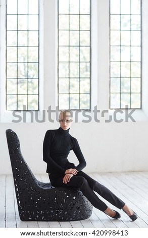 Sexy blond female in a black costume sits on a round black chair in  empty room.