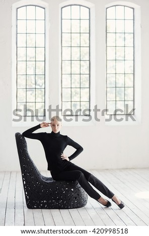 Sexy blond female in a black costume sits on a round black chair in  empty room. - stock photo