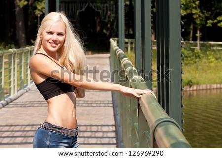 Sexy blond lady at the bridge - stock photo