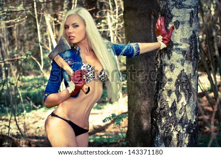 Sexy blond model with an axe in the forrest - stock photo