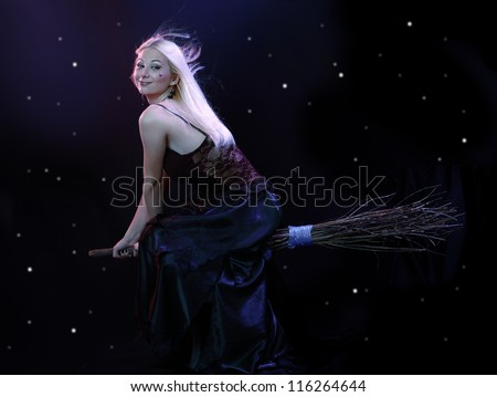 Sexy blond witch flying on broom on a dark sky with stars - stock photo