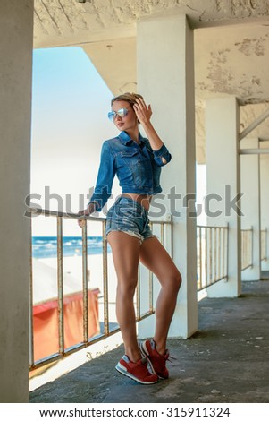 Sexy blond woman in jeans shorts and t-shirt posing over seaside. - stock photo