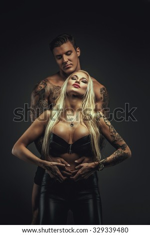 Sexy blond woman in underwear posing with muscular tattooed man.