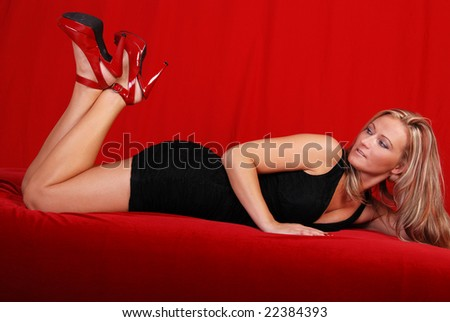 Sexy blond woman laying on her front on red velvet material, she is looking behind her at  her shoes.