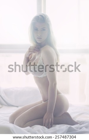 Sexy blond woman posing in white bed - stock photo
