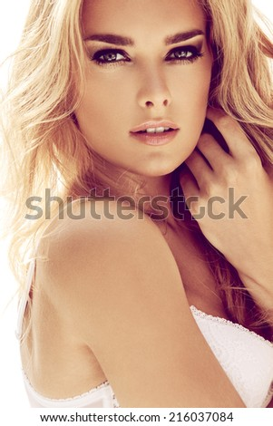 Sexy blond woman posing in white bed, the wind fluttering hair. - stock photo