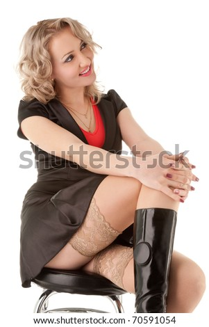 Sexy blond woman sitting on the bar chair isolated