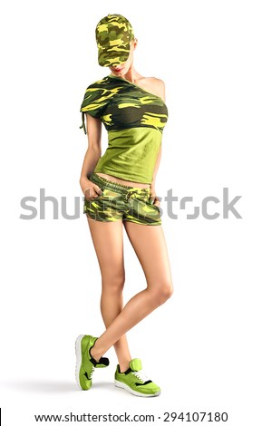 Sexy blond woman wearing military camouflage style clothing and cap. Seductive Army girl looking down with hands in pockets. Red lips and pigtail hairstyle.  Isolated on white background, copyspace - stock photo
