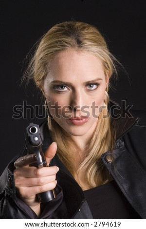 Sexy blond woman with gun in leather jacket on a black background