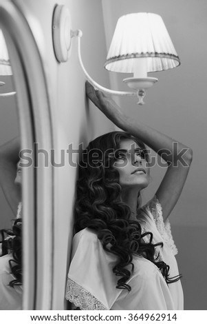 Sexy blonde bride in white robe posing near a mirror while preparing for the wedding ceremony b&w