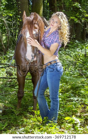Sexy blonde cowgirl holding her horse in the forest. - stock photo