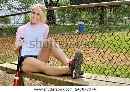 Sexy blonde female softball player in pink & white jersey shirt - sitting with legs extended on bench - bat at her side - smiling - stock photo