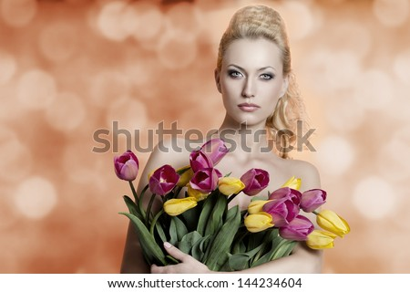 sexy blonde female taking bouquet of yellow and red tulips, looking in camera with pretty hair-style and make-up on bokeh background - stock photo