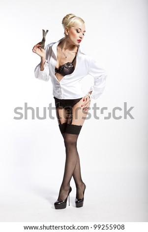 Sexy blonde girl in stockings on a white background holding a dollar - stock photo
