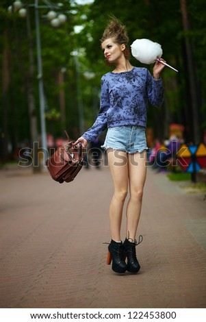 sexy blonde girl in summer park rides in shorts - stock photo