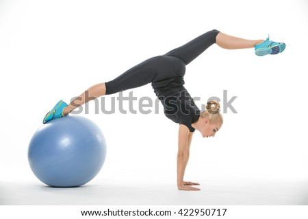 Sexy blonde girl in the sportswear with a blue fitball on the white background in the studio. She wears cyan-yellow sneakers, black pants and black t-shirt. She leans on her hands while her right leg