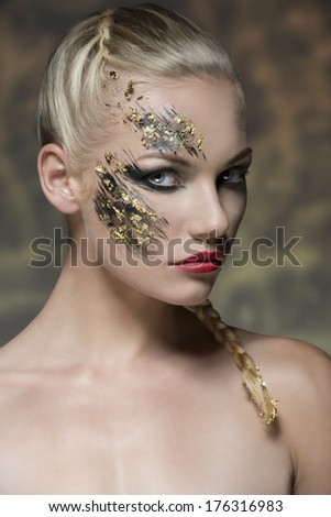 sexy blonde girl posing in beauty portrait with bride hair-style, naked shoulders and strange strong creative make-up